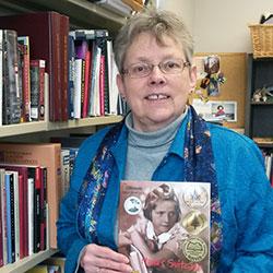 Photo of Lynne McKechnie holding a children's book