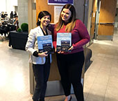 Bianca Huang and Meaghan Skinner show off the FIMS Career Conference official program.