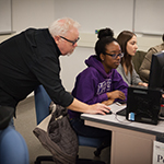 Instructor Mark Rayner assists students during class.