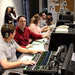 Student and staff work in the broadcast studio control room.