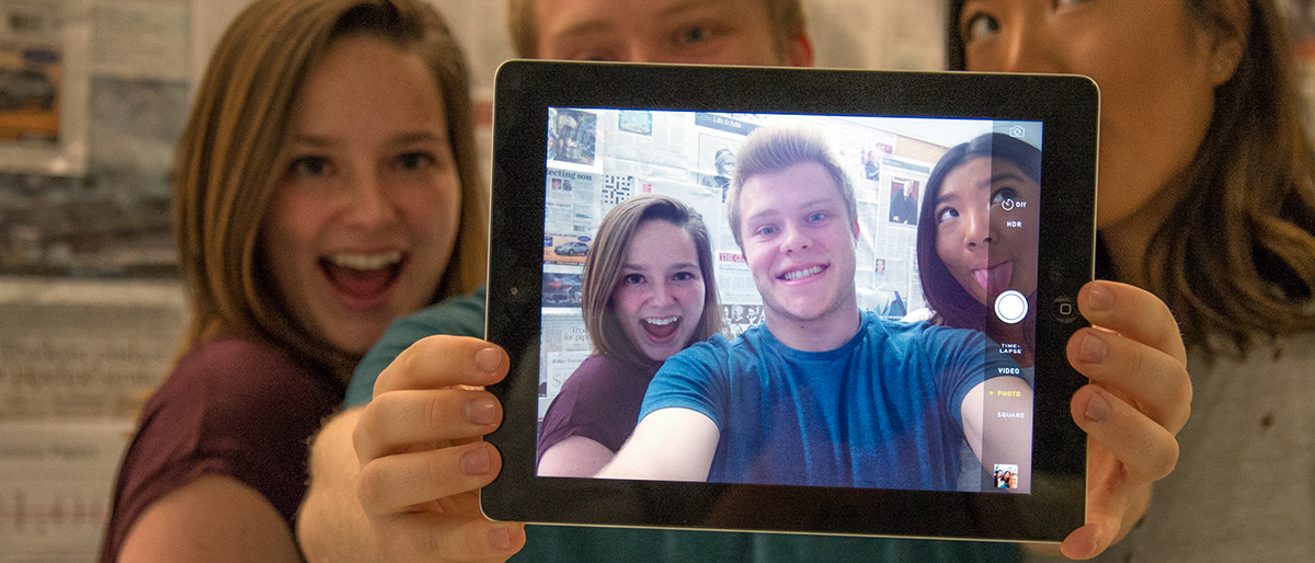 Photo of students posing with an iPad
